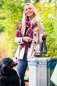 Frau entsorgt Hundekotbeutel