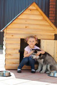 Mädchen mit Hund vor Hütte
