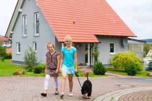 Zwei Mädchen mit Hund an Rollleine