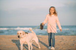 Blondes Mädchen hält Hund an Rollleine